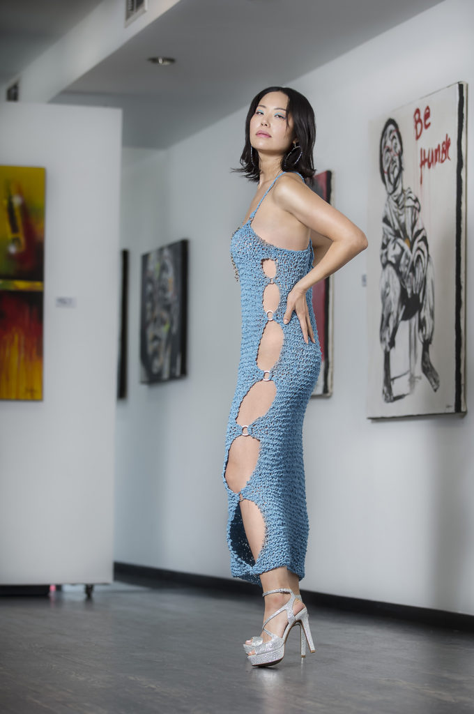 Female standing in a art gallery with art work hanging on the wall behind her with her habds pn her hips