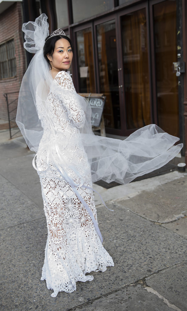 Female walking in the streets a a white wedding gown with veil on her head