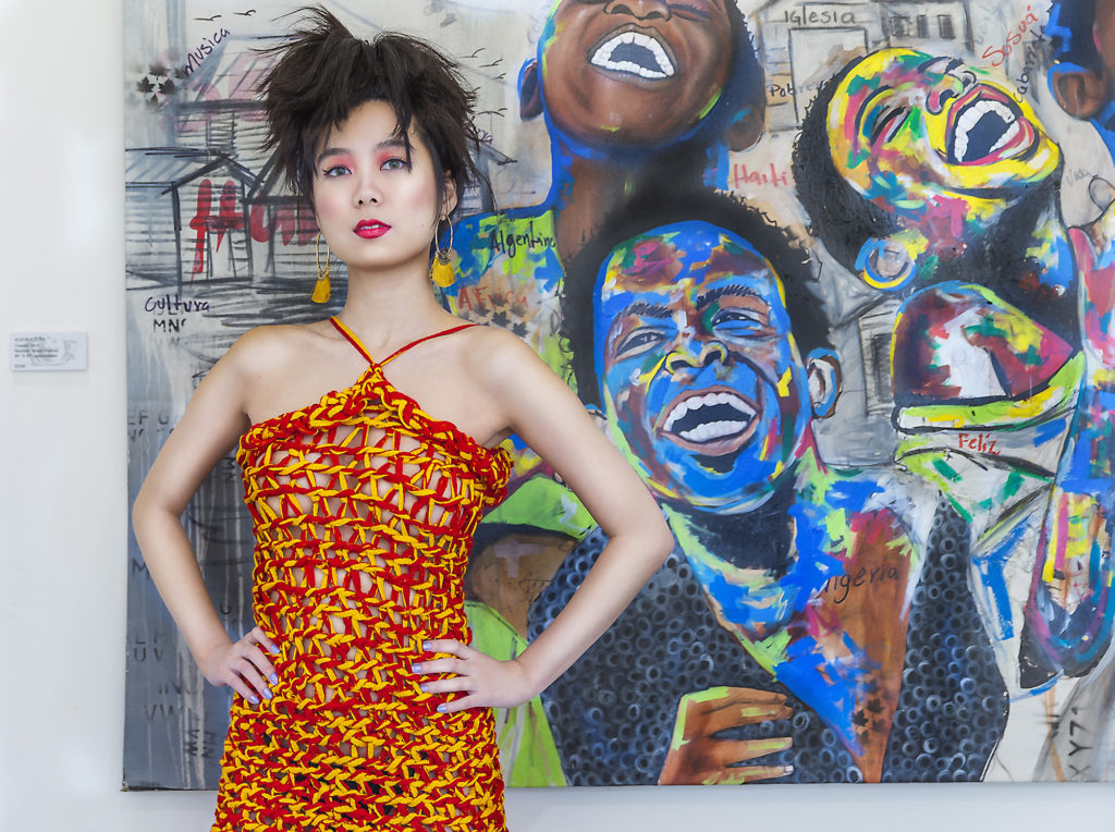 Female with her hands on her hips, dressed in a red and yellow string Crochet dress